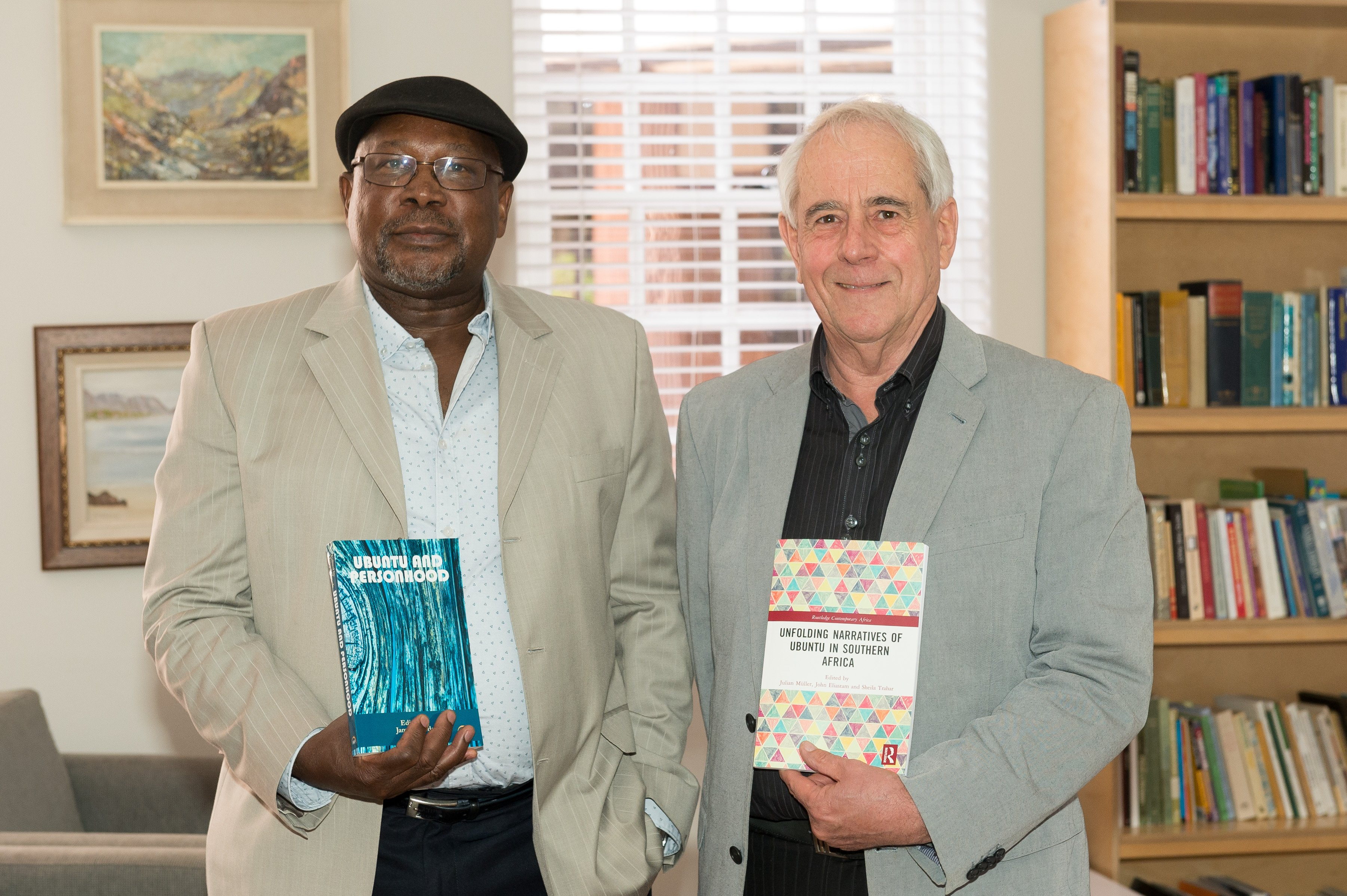 Professors James Ogude and Julian Muller (l-r) with the first books published in the Ubuntu Project.