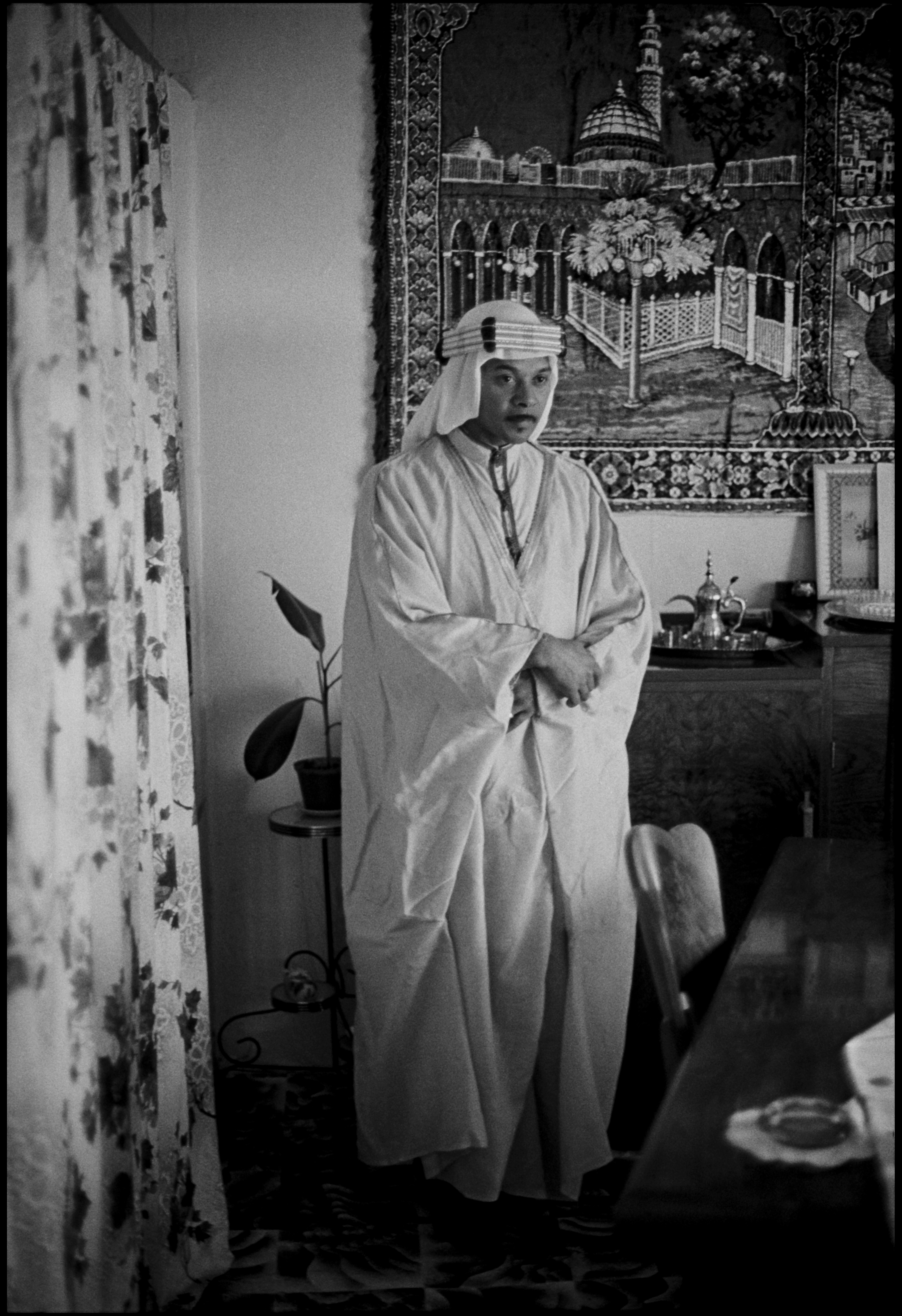a man who had performed the hajj pilgrimage in the 1970s poses for david brown in a traditional arab outfit